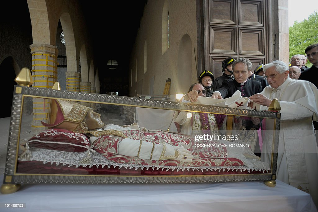 This file picture taken on April 28, 2009 shows Pope Benedict XVI (R) covering the relic of Pope Celestine V with a stole during his papal visit at St Maria of Collemaggio church collapsed on April 6 after the earthquake in L'Aquila. Pope Benedict XVI announced on February 11, 2013 his resignation, while the last pope to have abdicated the papacy is Celestine V in 1294.
