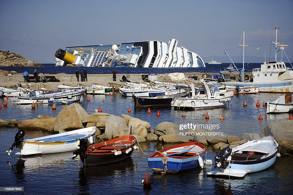 This file picture taken on January 15, 2012 shows small boats docked at the Giglio harbour behind the Costa Concordia after the cruise ship ran aground and keeled over off the Isola del Giglio, late on January 13. Almost a year ago, on January 13, 2012, the giant Italian cruise ship Costa Concordia ran aground near a Tuscan island and pitched leaving 32 people dead.