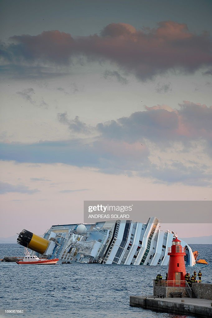 This file picture taken on January 17, 2012 shows the rising sun illuminating the cruise liner Costa Concordia aground in front of the harbour of Isola del Giglio after hitting underwater rocks on January 13. Almost a year ago, on January 13, 2012, the giant Italian cruise ship Costa Concordia ran aground near a Tuscan island and pitched leaving 32 people dead.