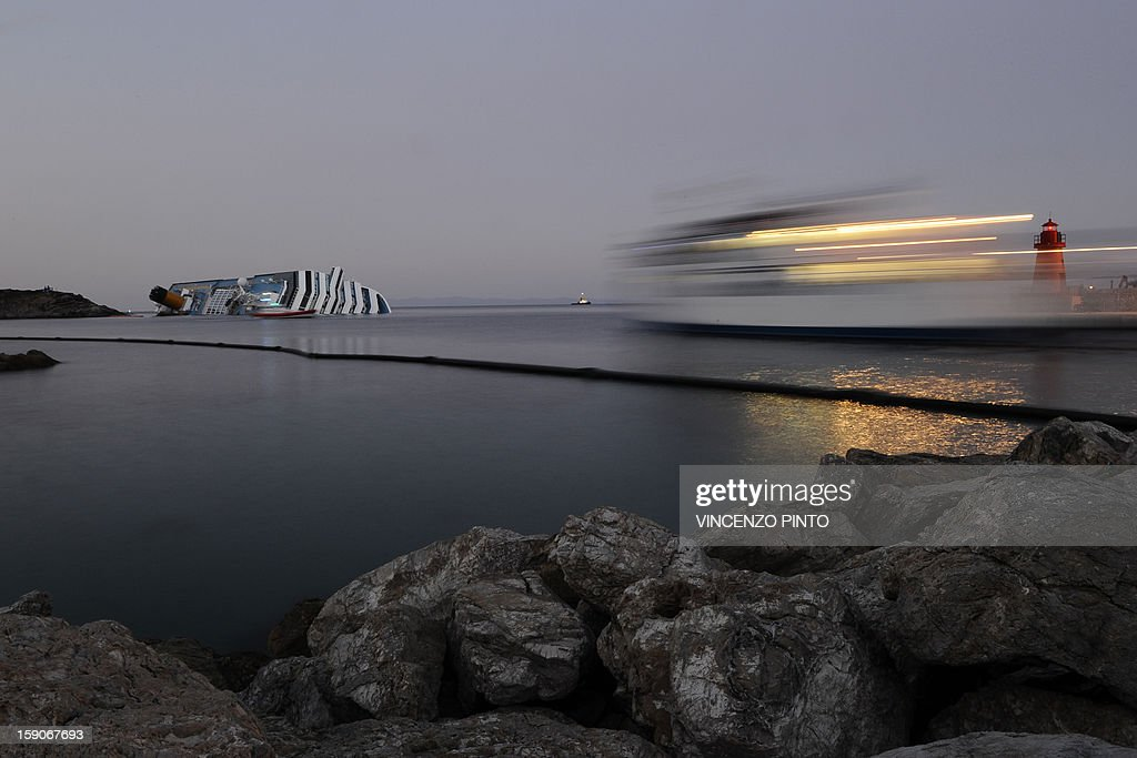 This file picture taken on January 18, 2012 shows a ferryboat (R) leaving the harbour of the Isola del Giglio (Giglio island) on as the cruise liner Costa Concordia (L) lies aground after hitting underwater rocks on January 13. Almost a year ago, on January 13, 2012, the giant Italian cruise ship Costa Concordia ran aground near a Tuscan island and pitched leaving 32 people dead. AFP PHOTO / FILES / VINCENZO PINTO