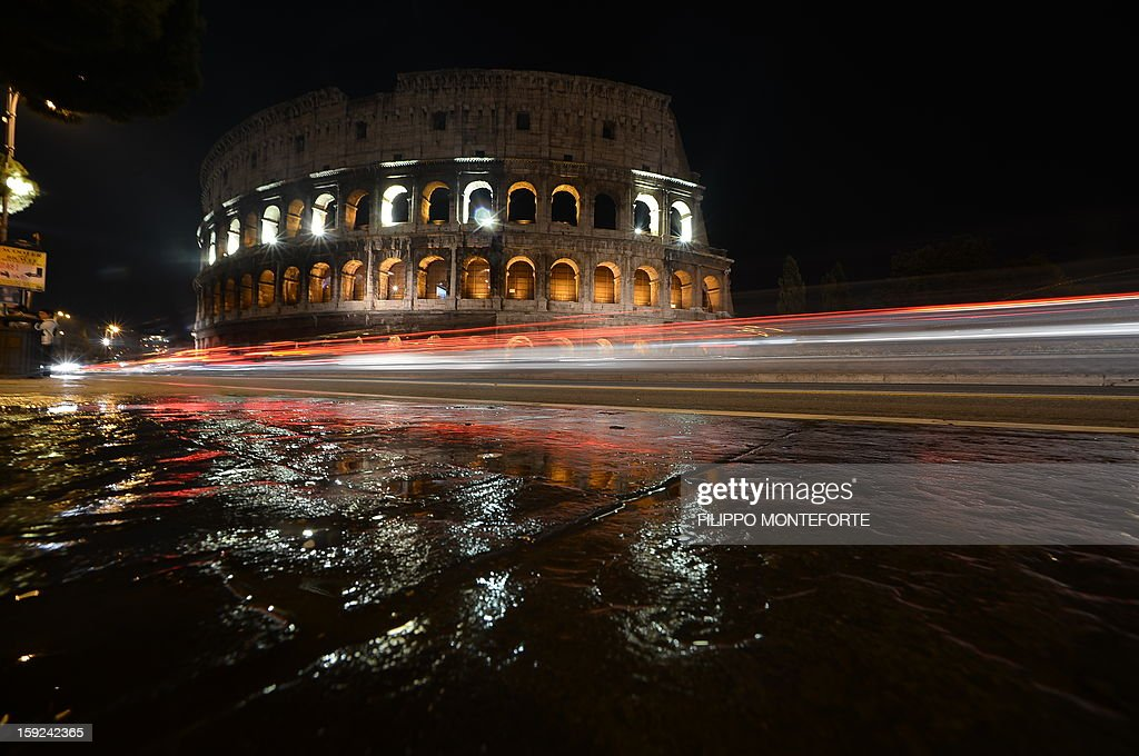 This file picture taken on November 25, 2012 in Rome shows the Colosseum illuminated on on the occasion of the International Day for the Elimination of Violence against Women. Italian archaeologists said on January 9, 2012 they have found brightly coloured fragments of frescoes depicting heroic and erotic scenes inside a corridor of the Colosseum in Rome, along with samples of ancient graffiti. AFP PHOTO / FILES / FILIPPO MONTEFORTE