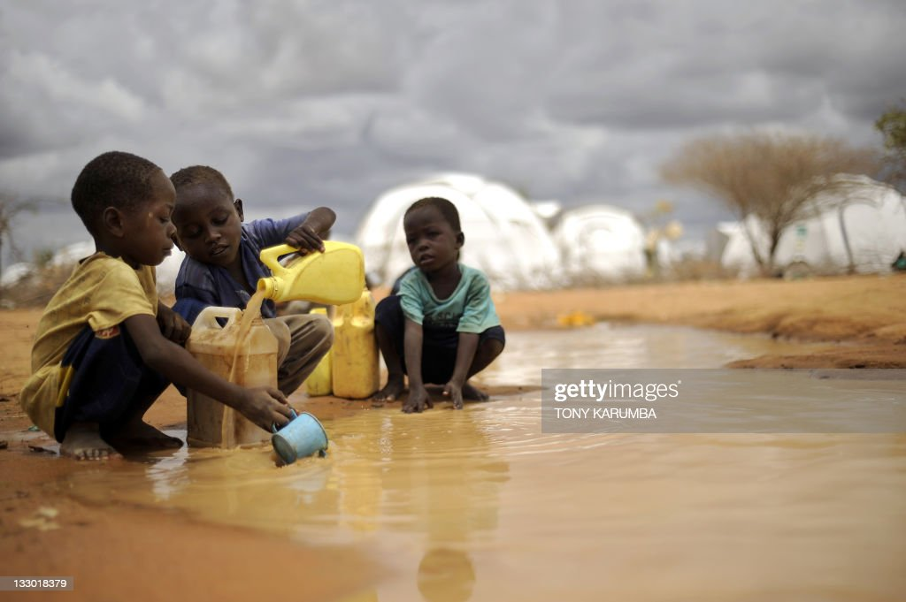 This file picture taken on October 16 shows Somali boys fetching water from a puddle that formed after rain at the IFO2 complex in the sprawling...