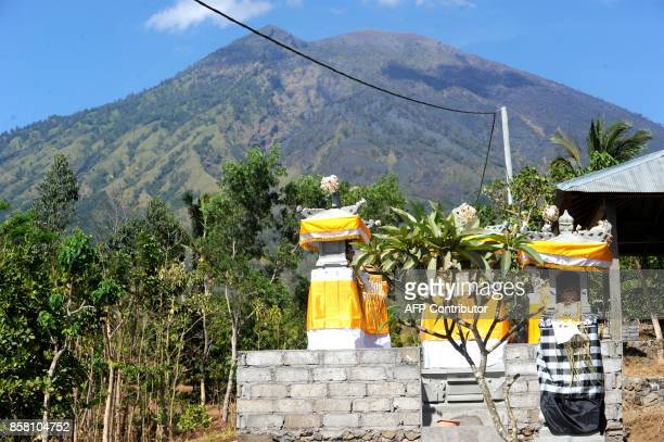 This general view shows a small Balinese shrine as Mount Agung volcano looms in the background in the Kubu subdistrict in Karangasem Regency on...