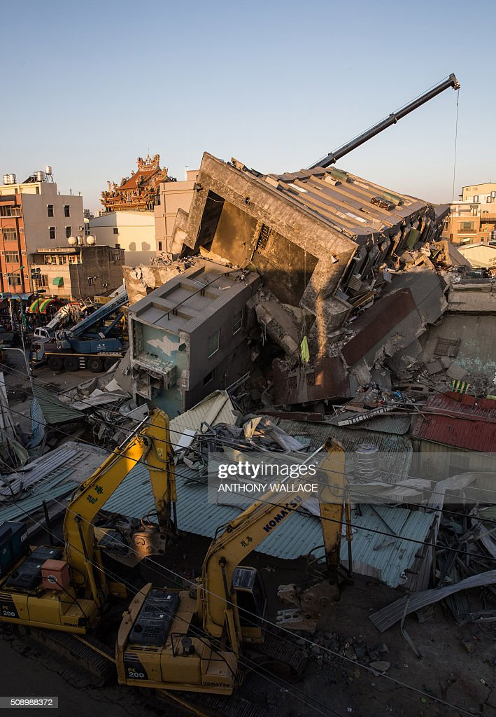 This general view shows cranes and heavy equipment being used for rescue operations at the site where a building which collapsed in the 6.4 magnitude earthquake, in the southern Taiwanese city of Tainan on February 8, 2016. Rescuers raced on February 7 to free around 120 people buried under the rubble of an apartment complex felled by an earthquake in southern Taiwan that left 34 confirmed dead, as an investigation began into the collapse. AFP PHOTO / ANTHONY WALLACE / AFP / ANTHONY WALLACE