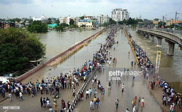 This general view shows Indian residents as they look at floodwaters on a major highway in Chennai on December 3 2015 Thousands of rescuers raced to...