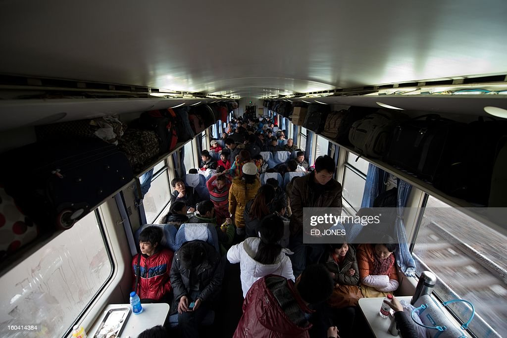 This general view shows Lunar New Year travellers aboard a crowded train bound for the southwestern Chinese city of Chongqing, a journey of 32 hours, as it departs from the West Railway Station in Beijing on January 31, 2013. The world's largest annual migration is underway in China with tens of millions across China boarding trains to journey home for Lunar New Year celebrations. Passengers will log 220 million train rides during the 40-day travel season as they criss-cross the country to celebrate with their families on February 10, but just as making the trip home can be laborious -- often lasting one or two days -- so can simply acquiring a seat on the train, and every year complaints arise about the inefficiency or unfairness of the system, although an initiative allowing travelers to purchase tickets online aims to curb long queuing times. AFP PHOTO / Ed Jones