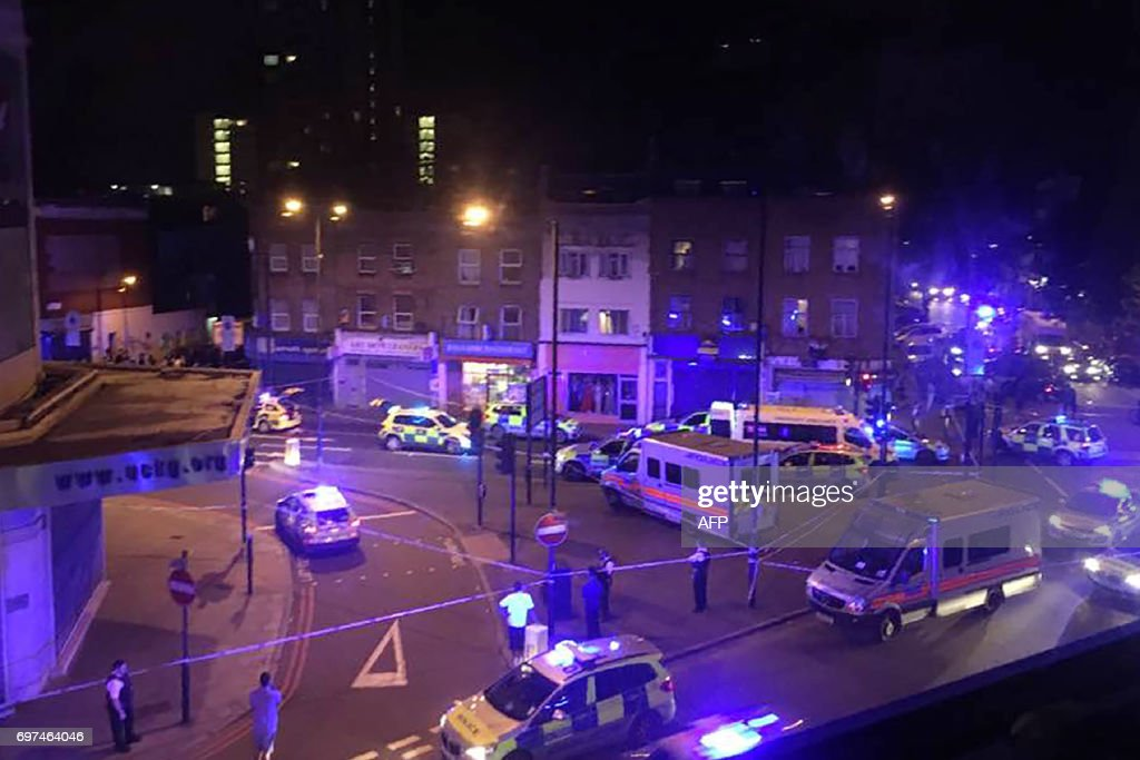 TOPSHOT - This general view shows police vehicles at the scene early on June 19, 2017, after a vehicle hit pedestrians in north London. One man was killed and eight people hospitalised when a van ran into pedestrians near a mosque in north London in an incident that is being investigated by counter-terrorism officers, police said on June 19. / AFP PHOTO / Chloe Jihyeon LEE