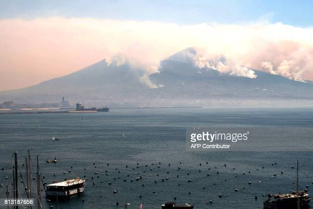 This general view shows smoke rising from fires on the slopes of the volcano of Mount Vesuvius east of Naples on July 12 2017 Across the country...