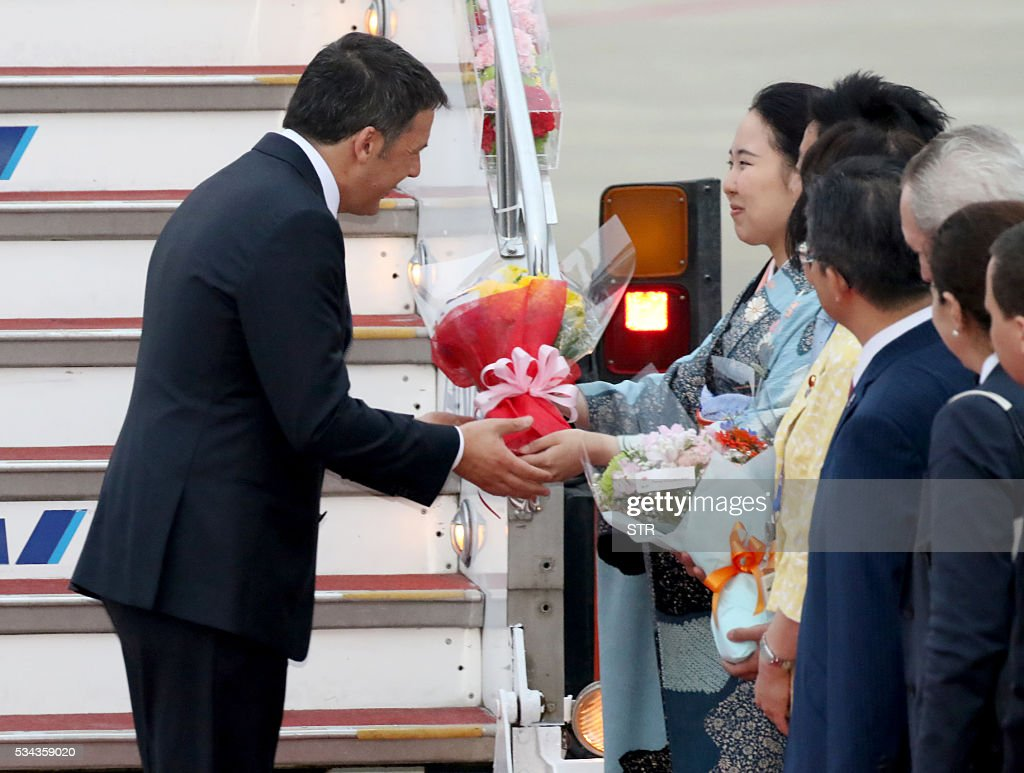 This hand out picture released by Foreign Ministry of Japan on May 26, 2016 shows Italian Prime Minister Matteo Renzi (L) receiving a bouquet of flowers from a woman wearing a Kimono, upon his arrival arriving at the Chubu Centrair International airport to attend the Group of Seven summit in Ise, Shima. World leaders kick off two days of G7 talks in Japan on May 26 with the creaky global economy, terrorism, refugees, China's controversial maritime claims, and a possible Brexit headlining their packed agenda. / AFP / Foreign Ministry of Japan / STR / RESTRICTED TO EDITORIAL USE - MANDATORY CREDIT 'AFP PHOTO / FOREIGN MINISTRY OF JAPAN' - NO