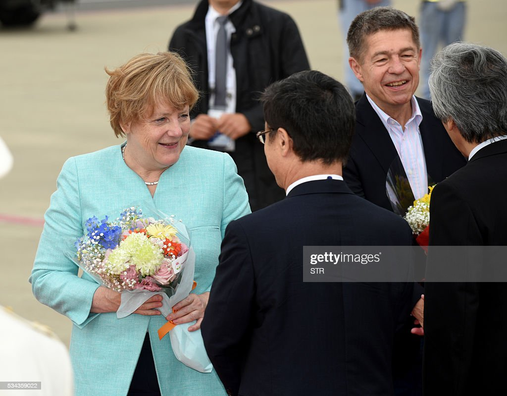 This hand out picture released by Foreign Ministry of Japan on May 26, 2016 shows German Chancellor Angela Merkel (L) and her husband Joachim Sauer (2nd R) being welcomed by well wishers upon their arrival at the Chubu Centrair International airport to attend the Group of Seven summit in Ise, Shima. World leaders kick off two days of G7 talks in Japan on May 26 with the creaky global economy, terrorism, refugees, China's controversial maritime claims, and a possible Brexit headlining their packed agenda. / AFP / Foreign Ministry of Japan / STR / RESTRICTED TO EDITORIAL USE - MANDATORY CREDIT 'AFP PHOTO / FOREIGN MINISTRY OF JAPAN' - NO