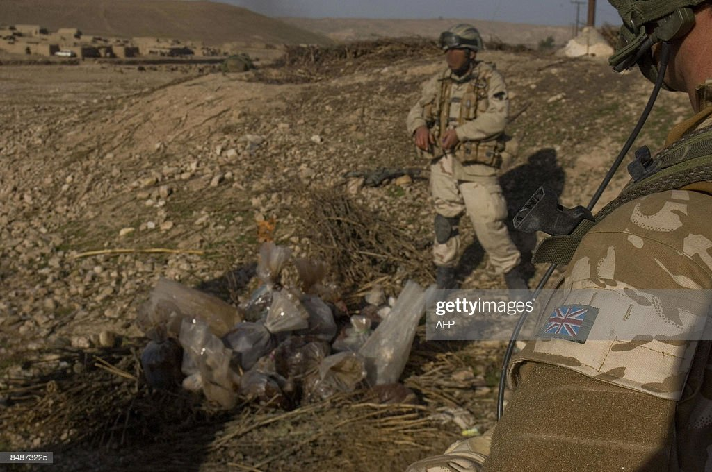 This handout image obtained on February 18 2009 from the Ministry of Defence shows a Royal Marine watching as a member of the ANA burns the drugs...