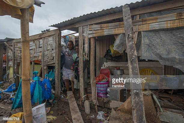 This handout image provided by UNICEF shows residents contend with storm damage in Mele village on March 15 2015 in Port Vila Vanuatu Cyclone Pam is...