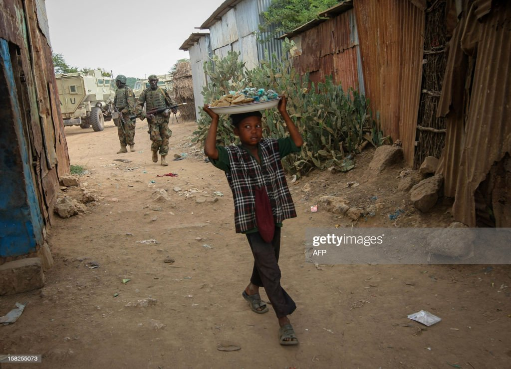 This handout photo released by the African Union-United Nations Information Support Team shows on December 12, 2012 shows a Somali boy carries a tray nuts and snacks near a market place in Jowhar in Middle Shabelle region north of the capital Mogadishu on December 11, 2012. African Union troops and Somali forces seized the formerly Islamist-held town of Jowhar Sunday, wresting control of one of the largest remaining towns held by the Al-Qaeda linked Shebab, officials said. The loss of Jowhar is a significant blow to the Shebab, who have lost a string of towns in recent months to the 17,000-strong AU force, as well as to Ethiopian troops who invaded Somalia last year from the west. RESTRICTED TO EDITORIAL USE - MANDATORY CREDIT 'AFP PHOTO / AU-UN IST PHOTO / STUART PRICE' - NO