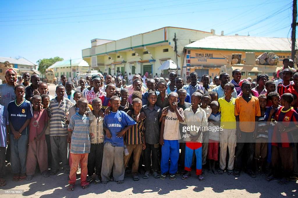 This handout photograph taken and released by the African Union-United Nations Information Support team on February 27, 2012, shows a crowd gathering in the centre of the central Somali town of Buur-Hakba following its capture by the Somali National Army (SNA), supported by forces of the African Union Mission in Somalia (AMISOM). The strategically important town on the Afgooye-Baidoa, corridor in Bay region, was liberated from Al-Qaeda-affiliated extremist group Al Shabaab early this morning without any resistance, marking a significant loss for the group. The town, located 64kms east of Baidoa, was a stronghold of the Shabaab where they extorted high levies of illegal taxation on the local civilian populations and used it as a base from where they planned and launched attacks against government forces and installations, AMISOM and the Somali population. Buur-Hakba is the latest in a string of significant territorial losses for the extremist group to SNA and AMISOM forces over the last 18 months, which has seen their area of influence and control over towns and areas across Somalia steadily decrease. AFP PHOTO / AU-UN IST / STUART PRICE CREDIT 'AFP PHOTO / AU-UN IST PHOTO / STUART PRICE' - NO