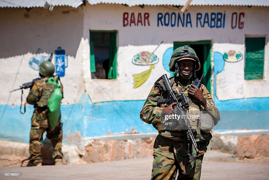 This handout photograph taken and released by the African Union-United Nations Information Support team on February 27, 2012 shows Ugandan soldiers serving with the African Union Mission in Somalia (AMISOM) standing guard in the centre of the central Somali town of Buur-Hakba following its capture by the Somali National Army (SNA), supported by AMISOM forcesp. The town, located 64kms east of Baidoa, was a stronghold of the Shabaab where they extorted high levies of illegal taxation on the local civilian populations and used it as a base from where they planned and launched attacks against government forces and installations, AMISOM and the Somali population. Buur-Hakba is the latest in a string of significant territorial losses for the extremist group to SNA and AMISOM forces over the last 18 months, which has seen their area of influence and control over towns and areas across Somalia steadily decrease. AFP PHOTO / AU-UN IST / STUART PRICE CREDIT 'AFP PHOTO / AU-UN IST PHOTO / STUART PRICE' - NO