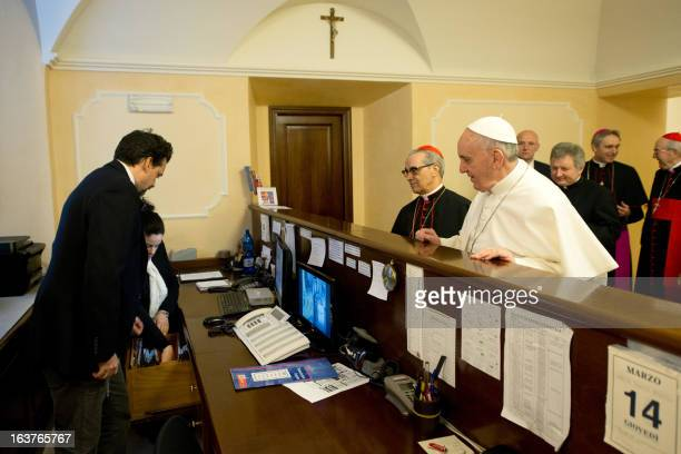 This handout picture released by the Press office shows Pope Francis at the reception desk of the Domus Internationalis Paulus VI residence as he...