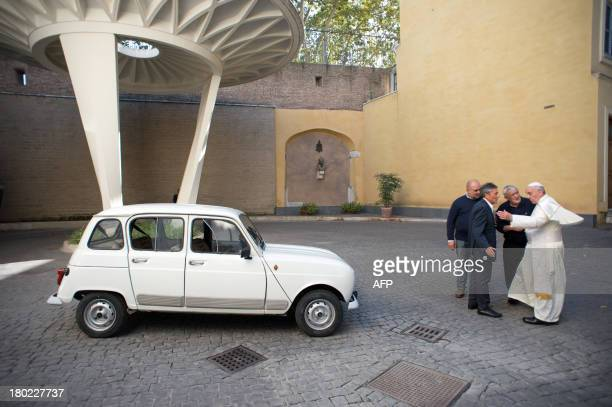 ROMANO' This handout picture released by the Vatican Press Office on September 10 2013 shows Father Don Renzo Zocca offering his white Renault 4L to...
