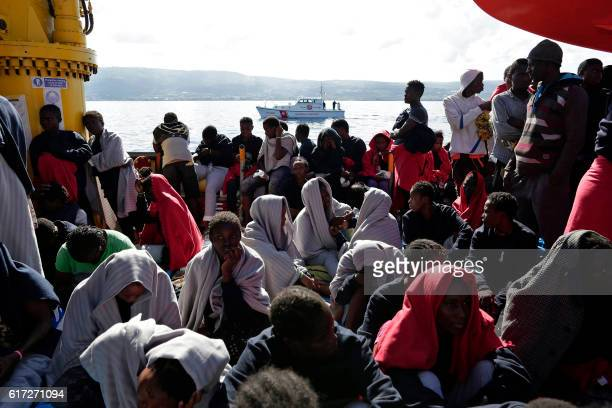 TOPSHOT This handout picture taken and released by the Italian Red Cross on October 22 2016 shows migrants landing in Vibo Marina after a rescue...
