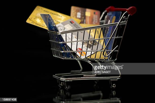 This illustration photo taken on December 22 in Paris shows credit cards in a miniature toy shopping cart AFP PHOTO / JOEL SAGET