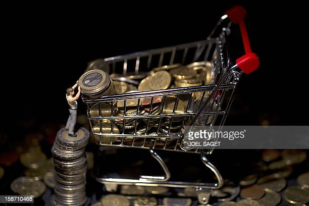 This illustration photo taken on December 25 in Paris shows a figurine next to a miniature toy shopping cart filled with coins AFP PHOTO / JOEL SAGET