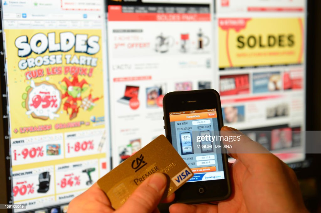 This illustration picture shows a person holding a credit card and a cell phone with a sales 'app', in front of websites advertsing for winter sales, on January 9, 2013, in Paris.