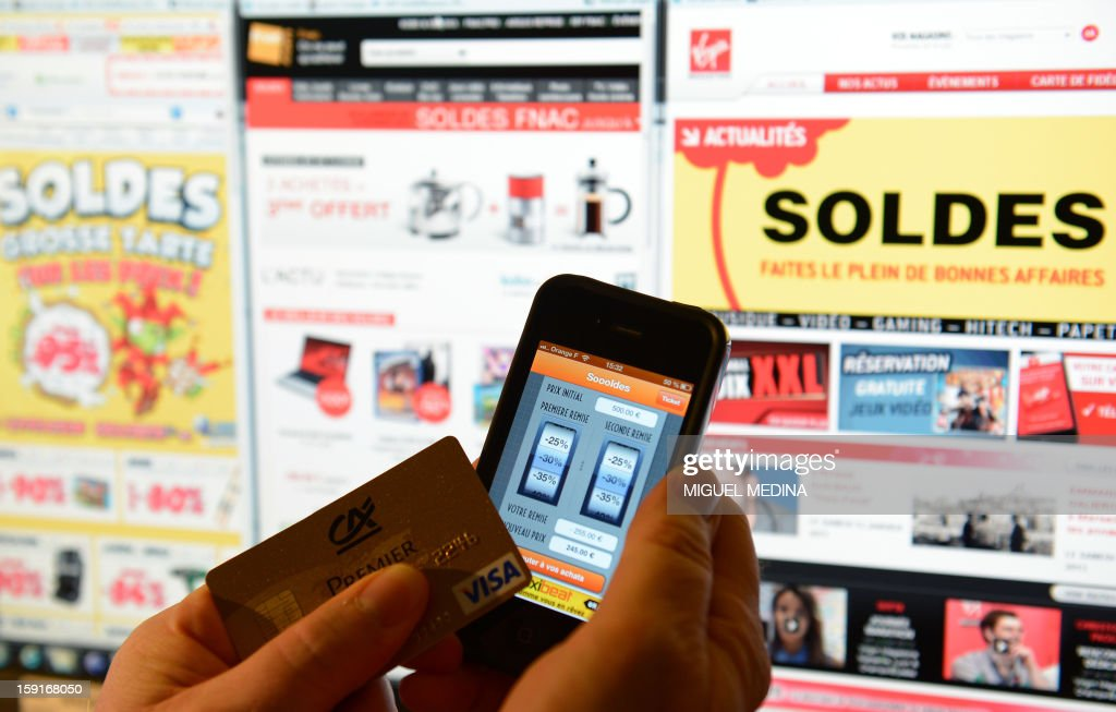 This illustration picture shows a person holding a credit card and a cell phone with a sales 'app', in front of websites advertsing for winter sales, on January 9, 2013, in Paris. AFP PHOTO / MIGUEL MEDINA / AFP PHOTO / Miguel MEDINA