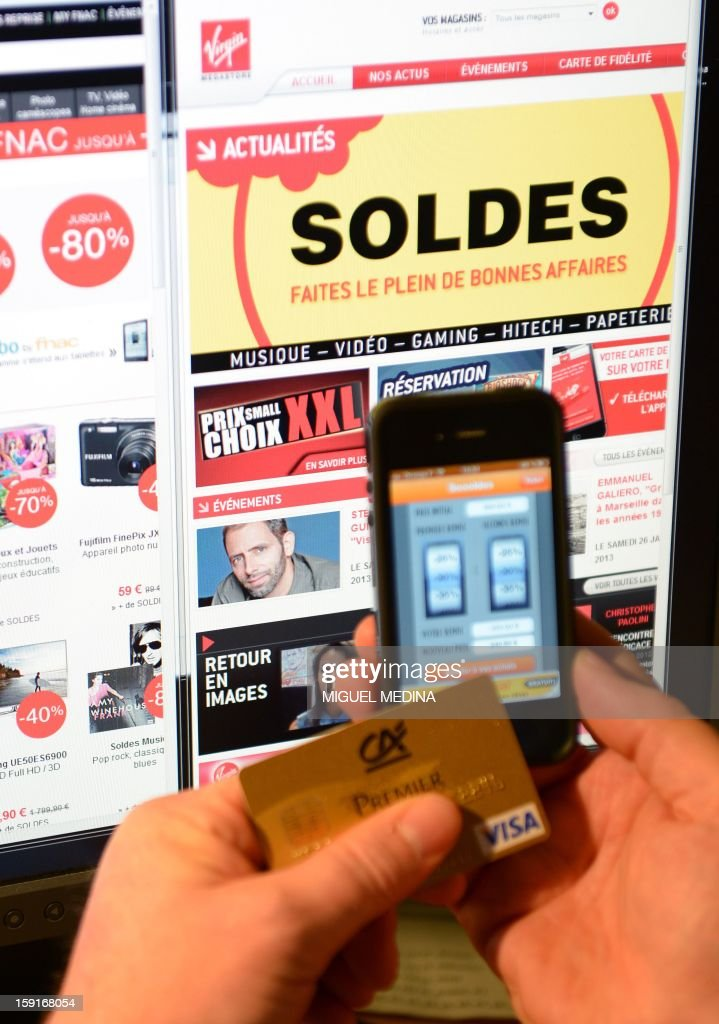 This illustration picture shows a person holding a credit card and a cell phone with a sales 'app', in front of websites advertsing for winter sales, on January 9, 2013, in Paris. AFP PHOTO / MIGUEL MEDINA