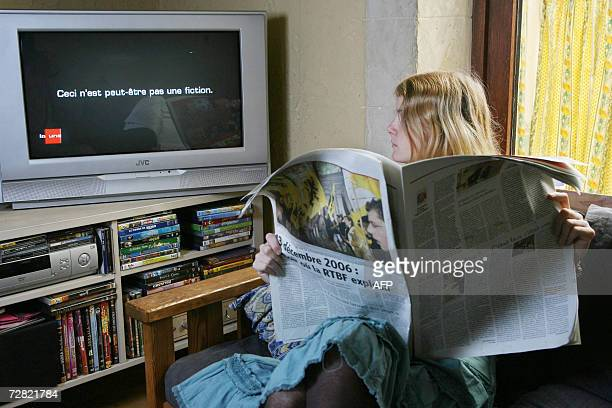 This illustration picture shows a teenager girl watching reading Le Soir newspaper with in the background the RTBF 1300 television journal commenting...
