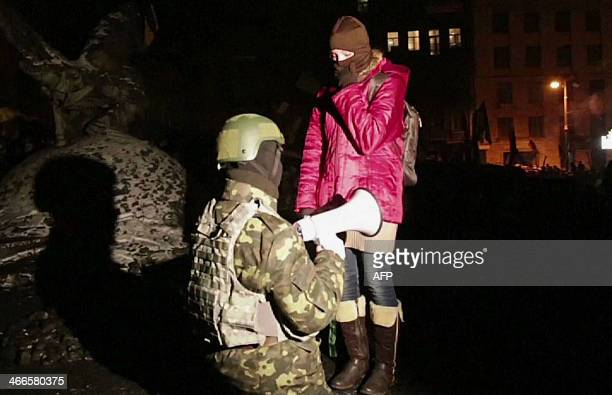 This image grab taken from AFP TV shows a protester making a wedding proposal to his girlfriend in a street close to Independence Square on which the...