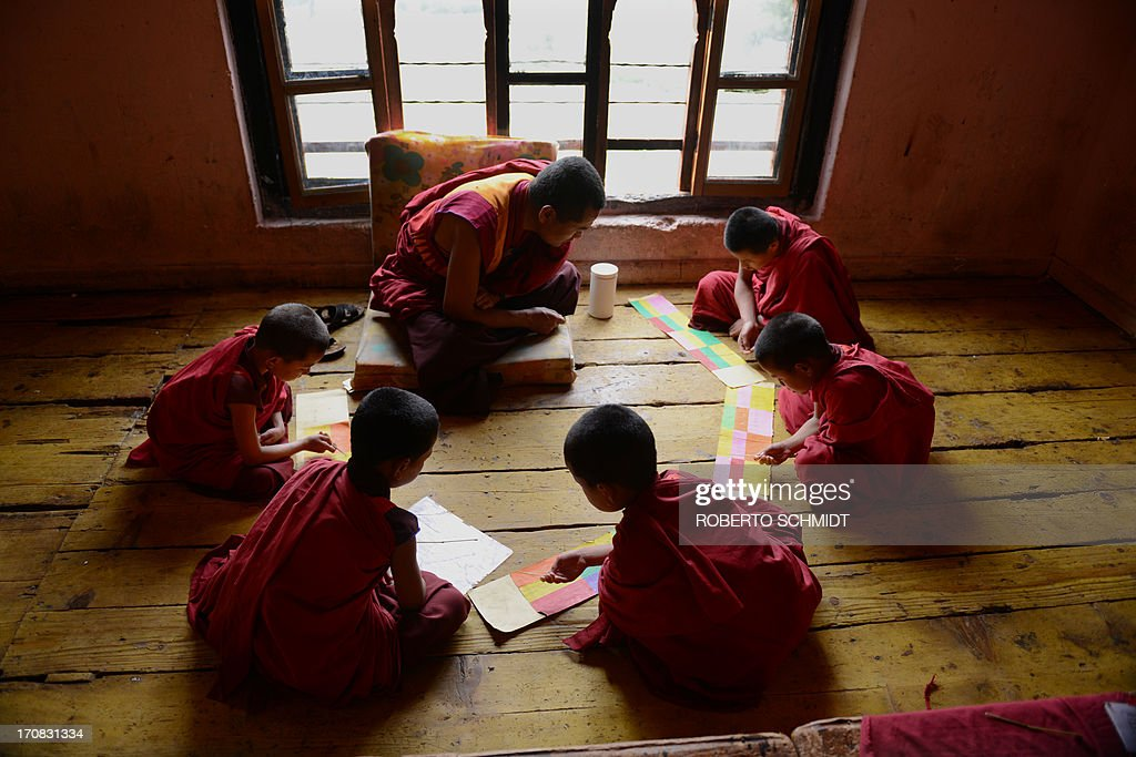 This image is part of of a photo package on children going to school around the world and it shows six-year-old monk apprentice Tandi Dorji (L) as he sits in a group with other young monks repeating holy scriptures in front of their teacher at a monastery in Thimpu, the capital of the Kingdom of Bhutan on June 4, 2013. Dorji is the youngest monk at the Buddhist monastery that overlooks the city and where over 200 monks learn among other things, about meditation, chants, holy scripture and about performing rituals honouring various bodhisattvas which are those being who have generated a spontaneous wish to attain Buddahahood for the benefit of all sentient beings. It is compulsory that all the students at the monastery to learn the holy scriptures by heart and spend a large part of their study time repeating it outloud to commit it to memory. AFP PHOTO/Roberto SCHMIDT