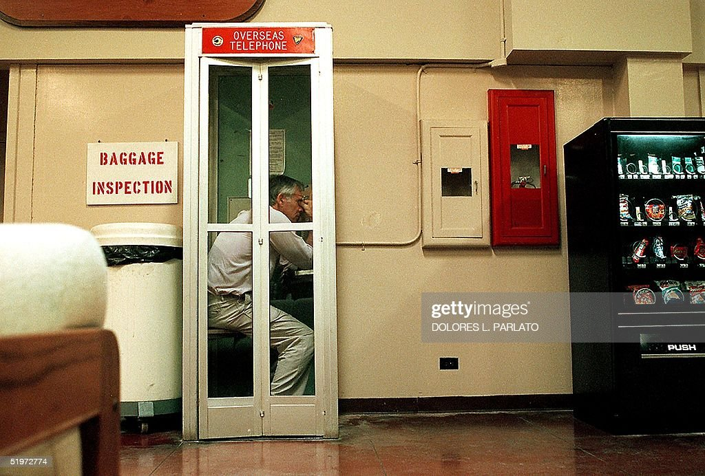 This image released 05 January 2001 by the US Navy shows US Secretary of the Navy Richard Danzig as he talks with his office in the Pentagon from a phone booth on Wake Island 13 October 2000 in the South Pacific regarding the 12 October 2000 bombing of the guided missile destroyer USS Cole in the port city of Aden, Yemen. Secretary Danzig was on an unprecedented trip to China when he received word of the terrorist attack. The emergency aircraft used to transport the Secretary back to Washington wasn't configured with a telephone, so during a refueling stop at Wake Island, the Secretary contacted his office on the first phone available.