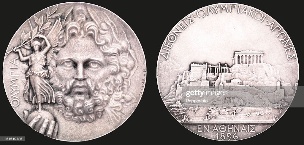 This image shows both sides of a winner's prize medal from the first modern Olympic Games at Athens in 1896. The medal was designed by Jules Chaplain, signed, struck in silver for first place (second place medals were bronze), the obverse with a portrait of Zeus with the globe in his right hand, upon which stands the goddess of victory, Nike, holding an olive branch, to the left in Greek script reads OLYMPIA, the reverse with a representation of the Acropolis and Parthenon, the inscription translated from the Greek reads INTERNATIONAL OLYMPIC GAMES, ATHENS, 1896. The original recipient of this victor's medal is unknown.