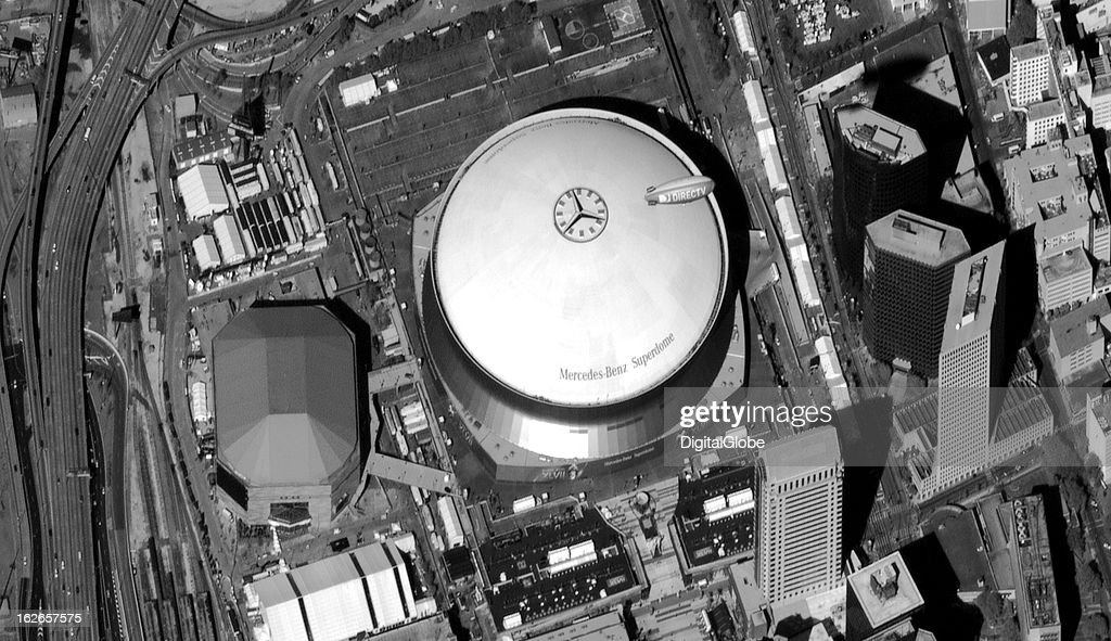 This image shows the Mercedes-Benz Superdome in downtown New Orleans, Louisiana, on the day the venue hosted the NFL Super Bowl XLVII. Signs for the Super Bowl can be seen along the bottom apron of the stadium, and the DirecTV blimp is flying overhead.