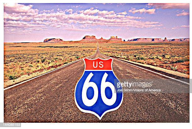 This is a digitally composed image with a US 66 road sign superimposed on the road to Monument Valley There is a desert landscape surrounding the road