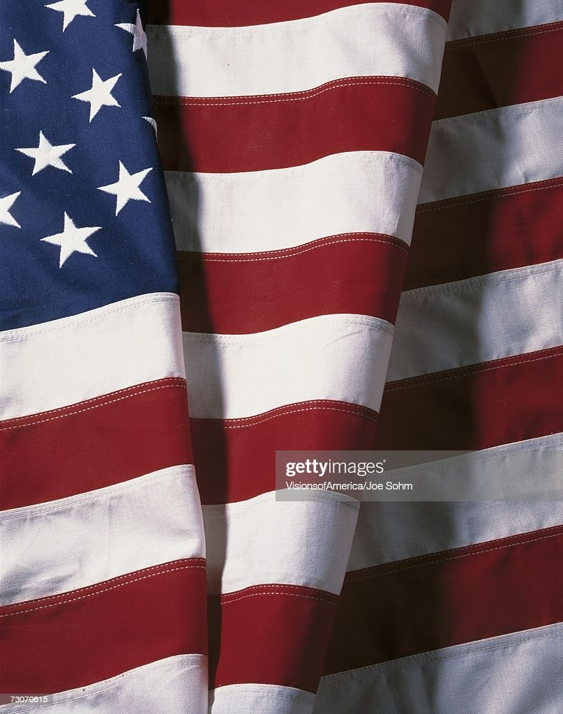 This is a folded American flag showing the stars against their blue field in the upper left hand corner. It is folded under in the center of the blue field of stars with the red and white stripes showing one more fold to the right of that. The flag is fol : Stock Photo