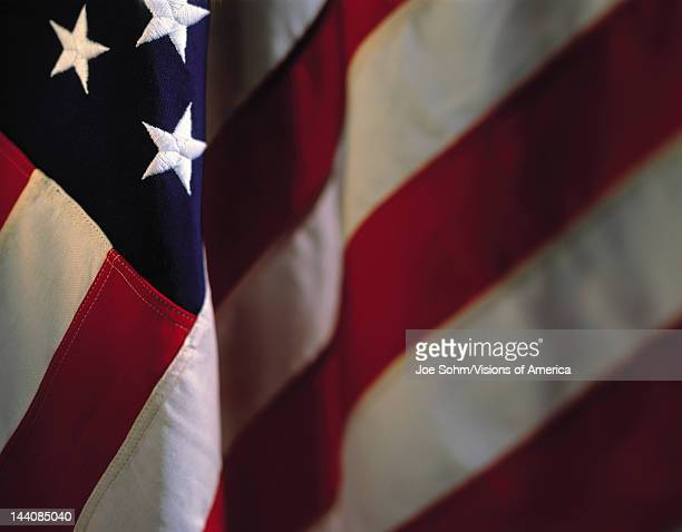 This is a hanging American flag There are three stars in the upper left hand corner with the stripes dropping down in a fold crossing diagonally...
