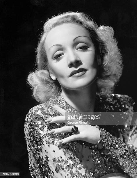 This is a head and shoulders photo of actress Marlene Dietrich in a blouse covered in sequins