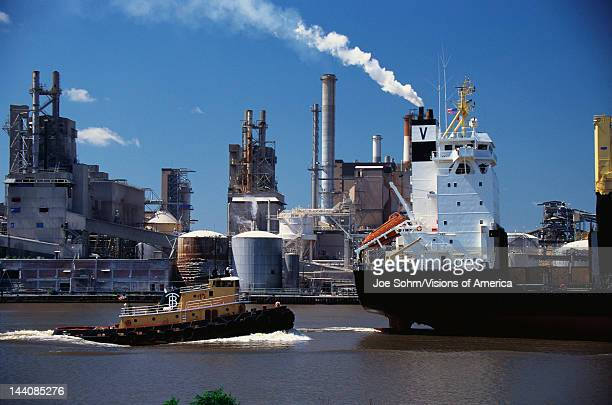 This is a Monrovia cargo ship on the Merkur River and Union Camp Paper Mill loading onto the cargo ship It is a paper mill with smokestacks...
