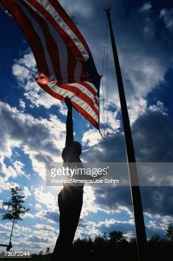 'This is a Park Ranger, raising the American flag on its flagpole. He is silhouetted, arm reaching up against a blue sky with clouds.' : Stock Photo