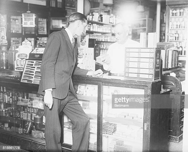 This is a photo of the interior of a drug store The druggist is discussing 'Cherry Coltsfoot Cough Ease' a medication with the customer