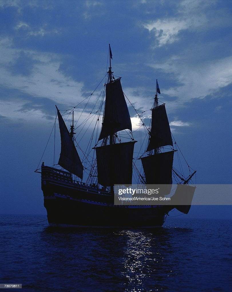 This is a replica of the ship Mayflower II. It demonstrates the first sailing in 1620 when the Pilgrims sailed to the New World. The ship shows full sails on a shimmering moonlit ocean against a dark blue night sky. : Stock Photo