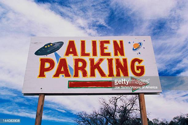 This is a road sign indicating where Alien Parking is This is the original UFO crash site in Roswell There are small UFOs on the sign with a large...
