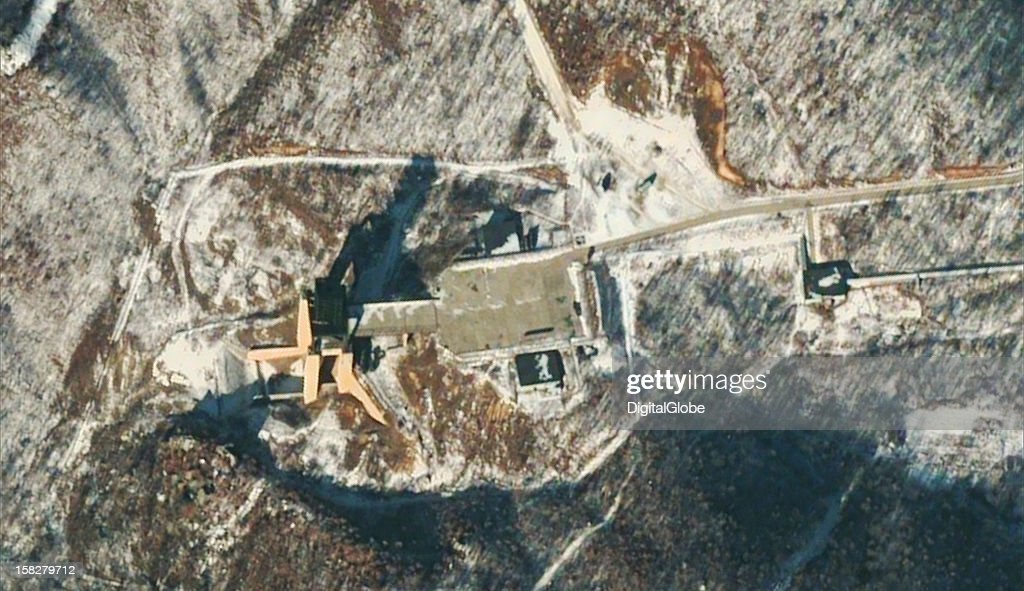 This is a satellite image of the vertical engine test stand at the Sohae Satellite Launch Station, 54 minutes after the launch of North Korea's second Unha 3 space launch vehicle. There are several vehicles visible in the area and on the facility apron.