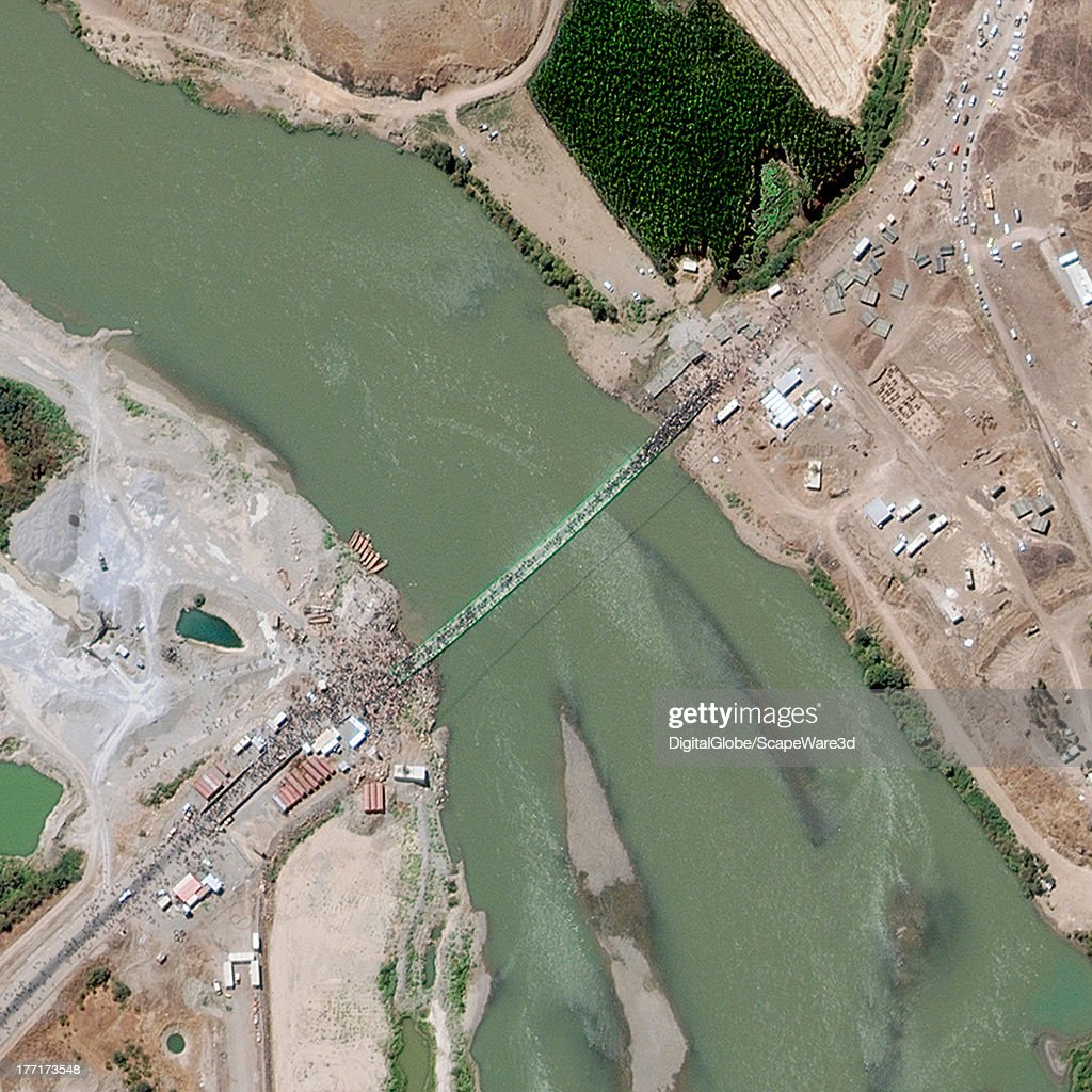 REFUGEES, TUNISIAN, SYRIA - AUGUST 17, 2013: This is a satellite image of thousands of Syrian refugees crossing a bridge over the Tigris River into northern Iraq.