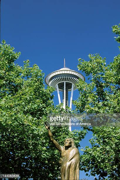 This is a statue of Chief Seattle in front of the Space Needle There is green summer foliage on the trees surrounding the statue