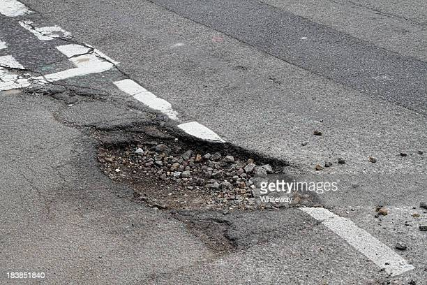 Bad repair pothole in road T-junction suffers frost damage