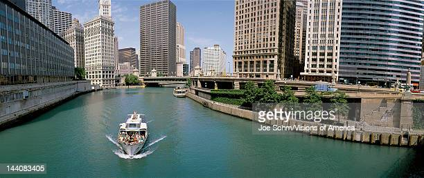 This is a tour boat on the Chicago River during summer The Chicago Tribune Building Chicago Sun Times Building and the IBM Building surround the river