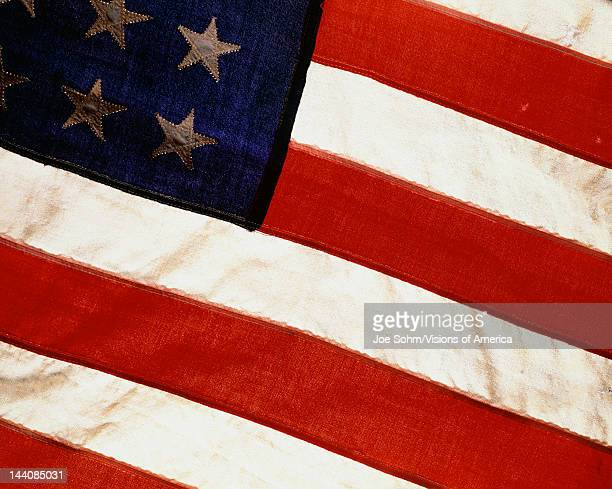This is a vintage American flag that has only 48 stars We see six of those stars against their blue field coming out diagonally from the upper left...