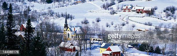 This is an aerial view of East Orange There is a black steepled church and a small village The village is covered in snow with houses spread across...