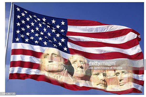 This is an American flag waving in the wind set on a flagpole against a blue sky The four presidents of the Mt Rushmore National Monument are...